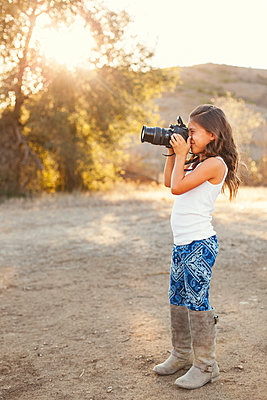 Side view of girl standing on field and photographing with camera - p1166m1088400f by Angie Wheeler