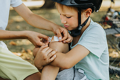 Boy putting bandage on younger brother knee sitting in public park - p300m2226856 by Mareen Fischinger