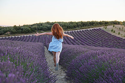 Girl running through lavender field - p312m1495440 by Lina Arvidsson