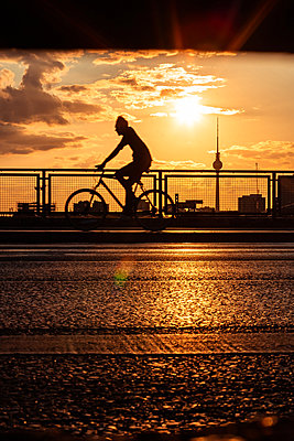Silhouette of man cycling on bridge with Fernsehturm Berlin in background during sunset - p623m2271900 by Pablo Camacho