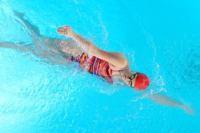 Teenage girl doing front crawl in swimming pool - p924m807059f by Pete Saloutos