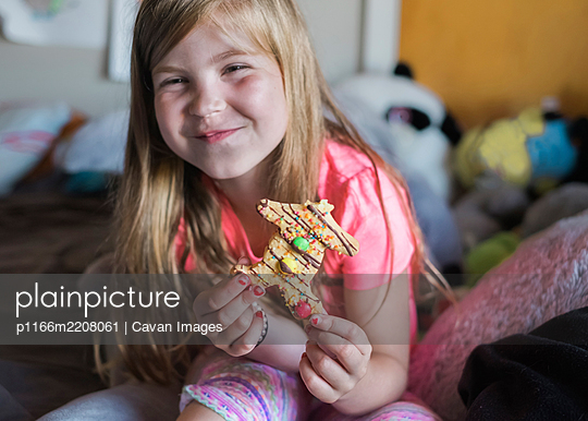 Young girl smiling and eating a gingerbread man in her bedroom - p1166m2208061 by Cavan Images