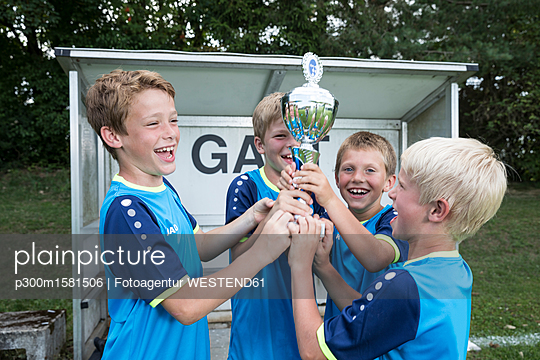Young football players cheering with cup - p300m1581506 by Fotoagentur WESTEND61
