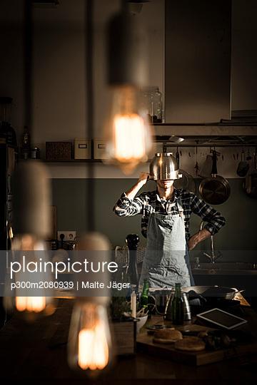Man with apron standing in kitchen, wearing colander as helmet - p300m2080939 by Malte Jäger
