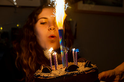 Young woman blows out candle on cake, stay at home due to Covid-19 - p1057m2185218 by Stephen Shepherd
