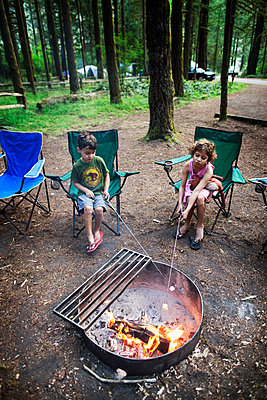 Children roasting marshmallows over fire pit in forest - p1166m1099593f by Cavan Images