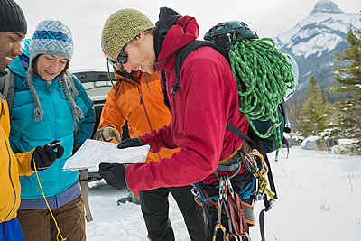 Group of friends looking at map in mountains - p1192m1043538f by Hero Images
