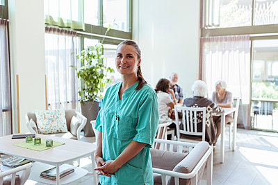 Portrait of smiling female healthcare worker with senior people in background at nursing home - p426m2072551 by Kentaroo Tryman