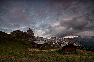 Dark clouds on green meadows and huts of the Odle mountain range seen from Seceda, Val Gardena, Trentino-Alto Adige, Italy, Europe - p871m1221566 by Roberto Moiola