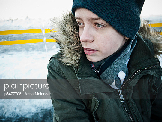 Serious boy, aged 13, in winter clothes   - p8477708 by Anna Molander