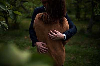Mid section of romantic couple hugging in orchard at dusk - p924m1197615 by Kymberlie Dozois Photography