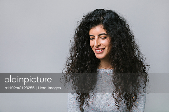 Portrait smiling, happy woman looking down - p1192m2123255 by Hero Images