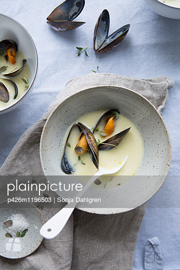 Directly above shot of mussel soup in bowl on table - p426m1196503 by Sonja Dahlgren