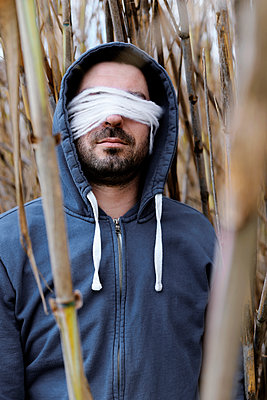 Blindfolded man in the reeds - p1521m2157605 by Charlotte Zobel