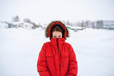 Sweden, Lapland, Hemavan, Portrait of young woman wearing red parka in winter - p352m1127117f by Matthew Phillips