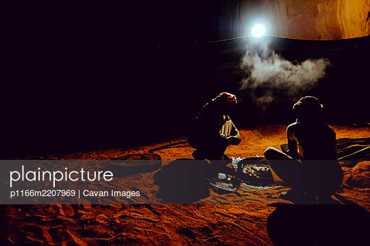 Two Bedouin men prepare a traditional cooked meal in Wadi Rum, Jordan - p1166m2207969 by Cavan Images