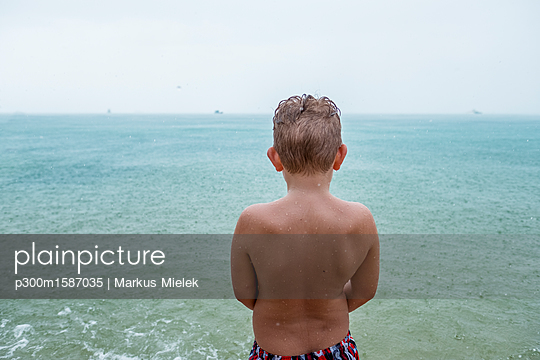 Back view of boy standing in front of the sea on rainy day - p300m1587035 von Markus Mielek