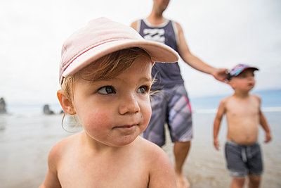 Portrait of cute one year old girl at the beach with brother and dad. - p1166m2157220 by Cavan Images