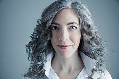 Portrait smiling Caucasian mid adult woman with curly gray hair - p1192m1213104 by Hero Images