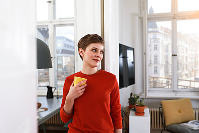 Woman standing in her comfortable home, drinking coffee - p300m1586949 by Florian Küttler