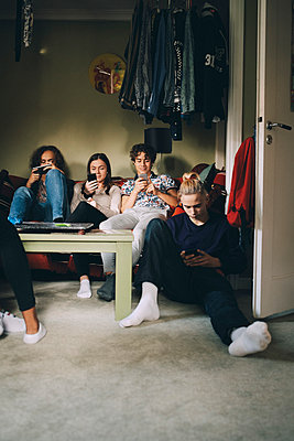 Full length of male and female teenagers using mobile phones while sitting at home - p426m2145457 by Maskot