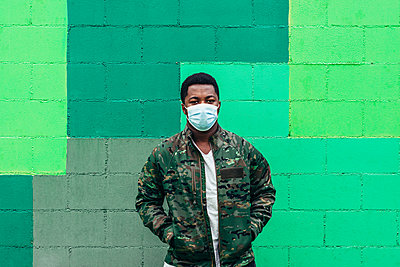 Afro American black boy on green wall background. Dressed in military jacket and face mask. - p1166m2254950 by Cavan Images