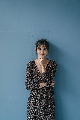 Woman with flower dress leaning against wall, portrait - p300m2023864 von Joseffson