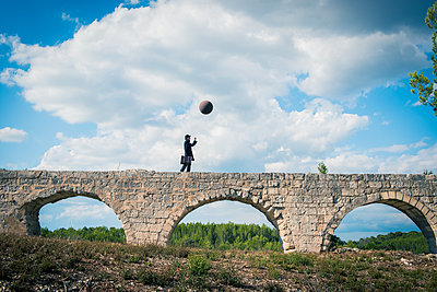 Man on aqueduct playing with balloon - p829m1110852 by Régis Domergue