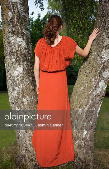 Frau steht in Baumgabel - p045m1169447 von Jasmin Sander