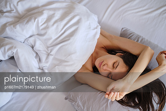 Young woman laying in her bed - p1607m2179149 by zhushman