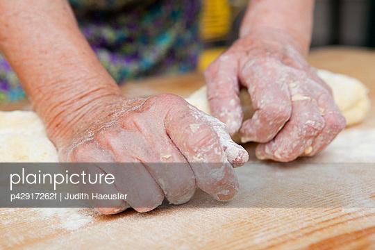 Close up of woman kneading dough - p42917262f by Judith Haeusler