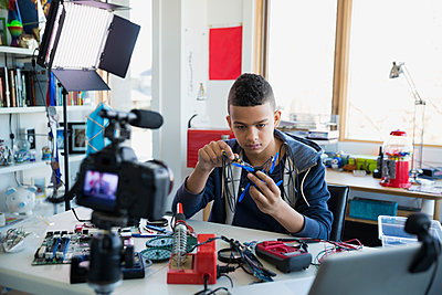 Boy videotaping circuit board assembly in bedroom - p1192m1129547f by Hero Images