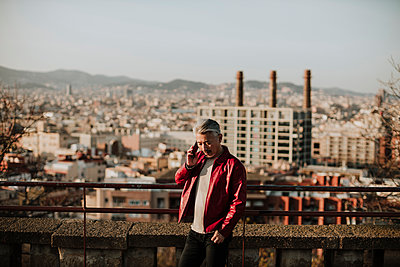 Mature man talking on smart phone while standing by retaining wall in city - p300m2274919 by Gala Martínez López