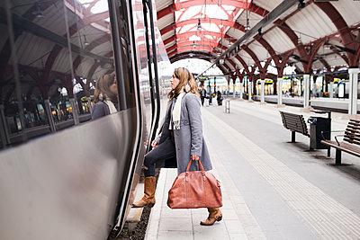 Woman entering train - p312m1471234 by Viktor Holm
