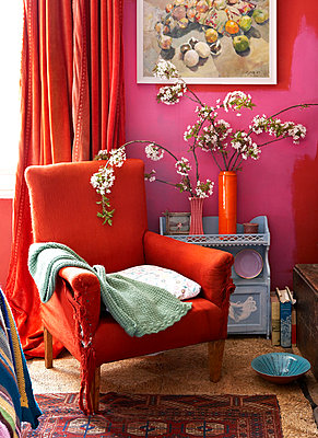 Red armchair with blanket and spring blossom in Isle of Wight living room;  UK - p349m920098 by Rachel Whiting