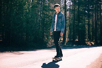 Caucasian man skateboarding on road near forest - p555m1531605 by Vladimir Serov