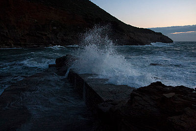 Wave crashing into shore at sunset - p583m1083776 by Kristina Williamson