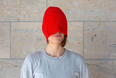 Young woman with woollen cap over her face - p975m2245764 by Hayden Verry