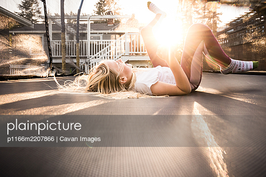 Young Girl Laying on Trampoline Laughing in Golden Evening Light - p1166m2207866 by Cavan Images