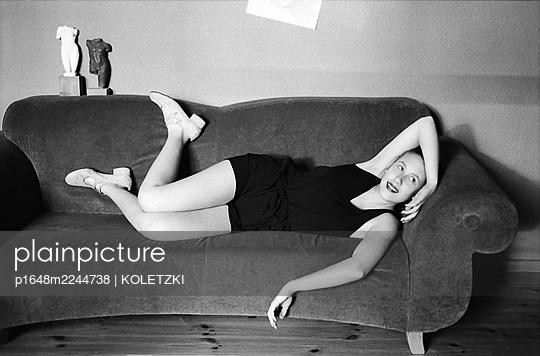 Woman lying on sofa - p1648m2244738 by KOLETZKI