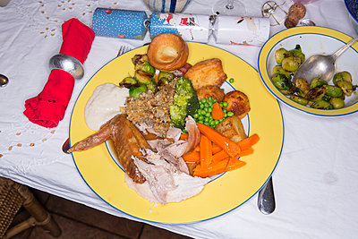 A christmas dinner plate full of turkey, potato and vegetables at family meal on christmas day. - p1057m1515167 by Stephen Shepherd