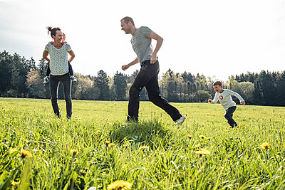 Family with two kids having fun together on a meadow in spring - p300m2166951 by Wilfried Feder