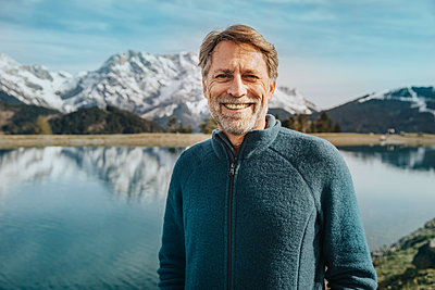 Smiling mature man standing against lake at Salzburger Land, Austria - p300m2266814 by Mareen Fischinger