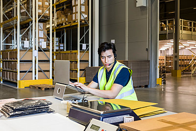 Confident young male customer service representative using laptop while sitting at desk in warehouse - p426m2018813 by Maskot
