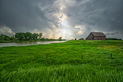 Abandoned barn with storm clouds converging overhead; Nebraska, United States of America - p442m2074091 by Robert Postma