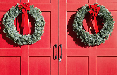 Christmas wreaths on red doors - p555m1452813 by Spaces Images