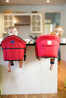 Rear view portrait of male and female toddlers looking back from kitchen counter - p924m1404228 by Sasha Gulish