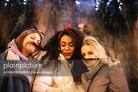 Young women making fake mustaches with their girlfriend‰Ûªs hair in city - p1166m2258309 by Cavan Images