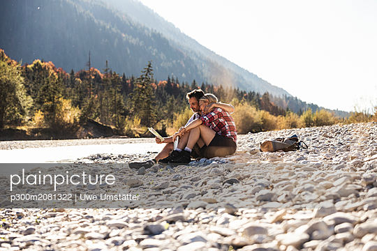 Austria, Alps, couple on a hiking trip having a break at a brook reading map - p300m2081322 by Uwe Umstätter
