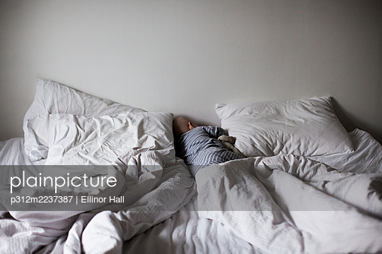 High angle view of baby sleeping on bed - p312m2237387 by Ellinor Hall